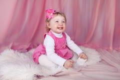 Lycklig le rolig liten flicka som över ler och vilar på säng Arkivfoton