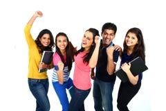Lycklig le stående av den unga indiern/asiatet Isolerat på den vita backgroen Arkivfoton