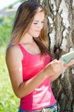 Lycklig le tonårig flicka- och minnestavladator Royaltyfri Fotografi