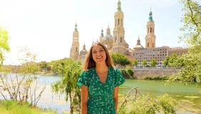 Lycklig le turist- kvinna i grön klänning som besöker Zaragoza, Spanien fotografering för bildbyråer