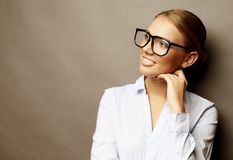 Lycklig le ung affärskvinna i exponeringsglas, över grå backgr royaltyfria bilder