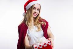 Lycklig le ung blond kvinna som bär den röda jultomtenhatten och ger julgåvaasken på vit bakgrund arkivbild