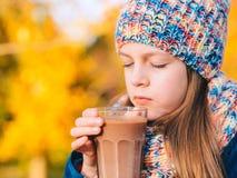 Lycklig le ung flicka som dricker choklad Arkivbilder