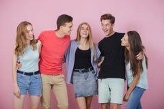 Lycklig le ung grupp av vänner som står som talar och skrattar tillsammans Bästa vän arkivfoto