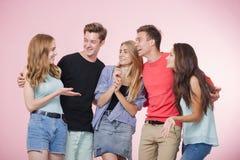 Lycklig le ung grupp av vänner som står som talar och skrattar tillsammans Bästa vän fotografering för bildbyråer