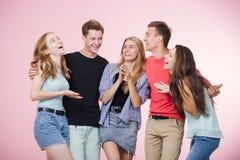 Lycklig le ung grupp av vänner som står som talar och skrattar tillsammans Bästa vän royaltyfri bild