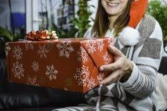Lycklig le ung härlig kvinna som rymmer och ger en julgåva royaltyfria foton