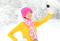 Lycklig le ung kvinna för modevinter som tar bild självståenden på smartphonen över snöig träd som bär den färgrika stack hatten Arkivfoton