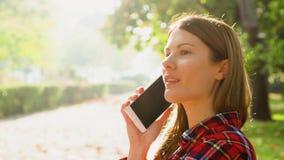 Lycklig le ung kvinna som tycker om naturen Att sitta på bänk i gräsplan parkerar samtal på hennes mobiltelefon lager videofilmer