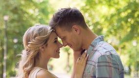 Lycklig le ung man och kvinna som att närma sig sig och kramar, långsam-mo lager videofilmer