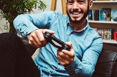 Lycklig le ung stilig man som hemma spelar videospel och har gyckel royaltyfri bild