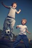 Lycklig lek för pojke två i fotboll Fotografering för Bildbyråer