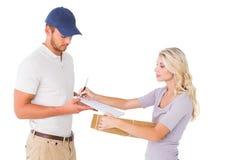 Lycklig leveransman som ger packen till kunden Royaltyfri Fotografi