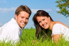 lycklig liggande äng för par royaltyfria foton