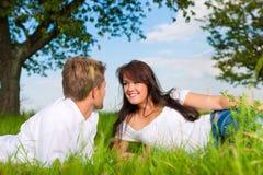 lycklig liggande äng för par royaltyfri bild