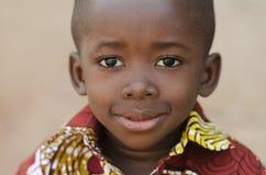 Lycklig liten afrikansk pojke som ler på kameraståenden royaltyfri fotografi