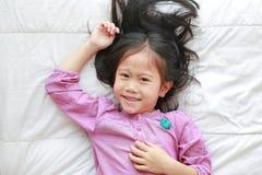 Lycklig liten asiatisk barnflicka som ligger på den vita filten på säng med att se kameran ovanf?r bl? tonad hj?lpmedelsikt arkivfoto
