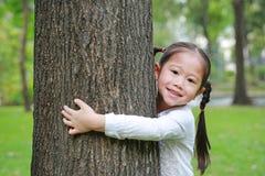Lycklig liten asiatisk barnflicka som omfamnar ett stort träd i trädgården arkivfoto