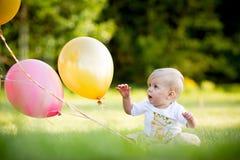 Lycklig liten blond caucasian flicka utanför med ballonger arkivfoton