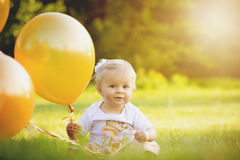 Lycklig liten blond caucasian flicka utanför med ballonger arkivbilder