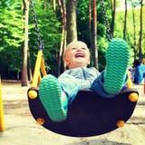 Lycklig liten blond pojke som har gyckel på en gunga Royaltyfri Bild
