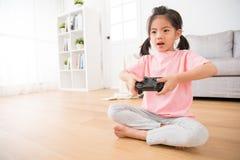 Lycklig liten dotterfokus på att använda den modiga styrspaken Arkivfoton