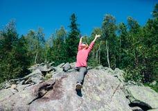 Lycklig liten flicka i berget med händer som lyfts till solen arkivfoton