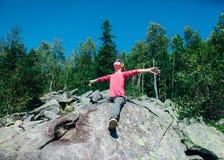 Lycklig liten flicka i berget med händer som lyfts till solen royaltyfri foto