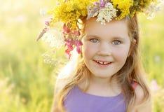 Lycklig liten flicka i blommakrona på solig sommaräng Royaltyfri Fotografi