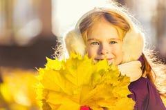 Lycklig liten flicka i earflaps med höstsidor Arkivbild