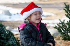 Lycklig liten flicka i en jultomtenhatt Arkivbild