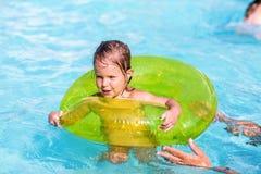 Lycklig liten flicka i en pöl in på den gröna livpreserveren som lär att simma fotografering för bildbyråer