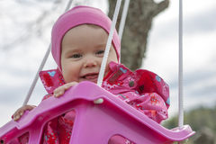 Lycklig liten flicka i en swing arkivfoto