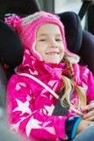 Lycklig liten flicka i ett bilsäte arkivfoton