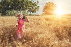 Lycklig liten flicka i ett fält av moget vete royaltyfri foto