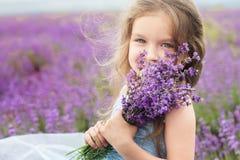 Lycklig liten flicka i lavendelfält med buketten
