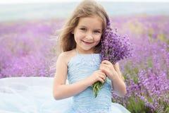 Lycklig liten flicka i lavendelfält med buketten royaltyfri bild