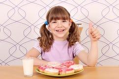 Lycklig liten flicka med den övre tummen och donuts Arkivfoto