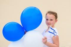 Lycklig liten flicka med den bl?a och vita flaggan f?r ballongans Israel arkivbild
