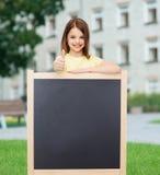Lycklig liten flicka med den tomma svart tavla Arkivbilder