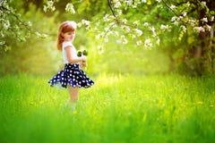 Lycklig liten flicka med en bukett av liljekonvaljer som har Royaltyfri Foto