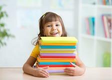 Lycklig liten flicka med en bunt av böcker Royaltyfri Bild