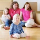 Lycklig liten flicka med en leksak i hennes nya hem Fotografering för Bildbyråer