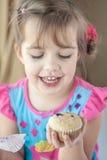 Lycklig liten flicka med en muffin Arkivfoto