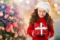 Lycklig liten flicka med gåvan nära julgranen arkivbilder