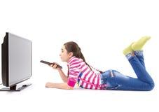 Lycklig liten flicka med hållande ögonen på tv för fjärrkontroll fotografering för bildbyråer