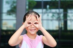 Lycklig liten flicka med handexponeringsglas framme av hennes ?gon royaltyfri foto