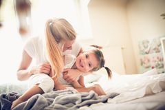 Lycklig liten flicka med hennes mamma royaltyfri bild