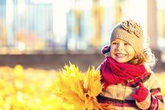 Lycklig liten flicka med höstsidor Arkivfoto