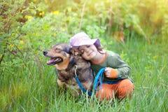 Lycklig liten flicka med hunden Fotografering för Bildbyråer